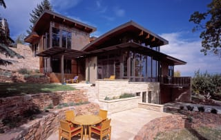 Green Custom Home exterior with stone patio and floor to ceiling windows