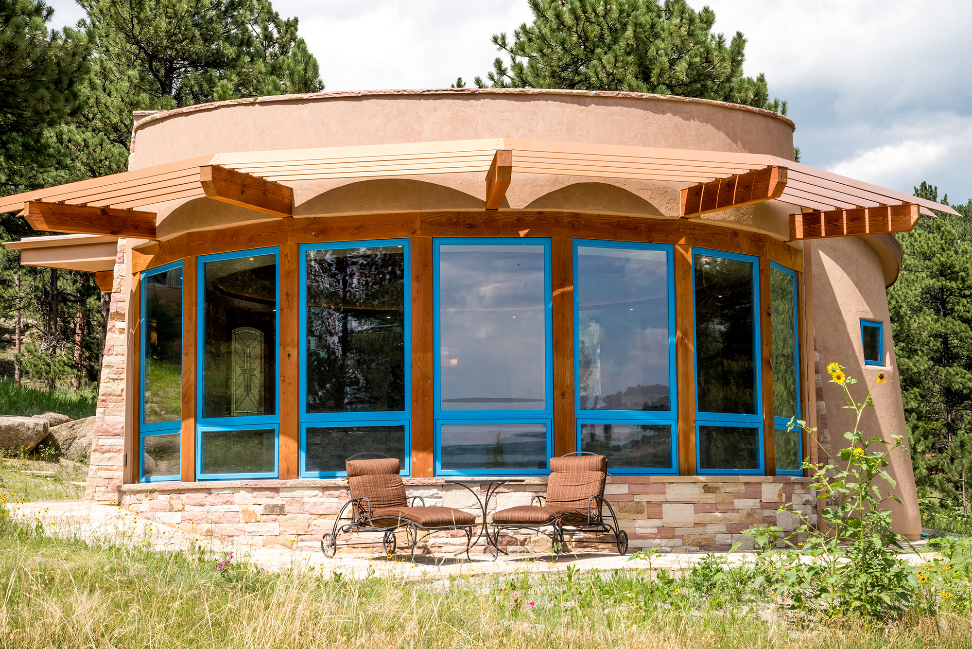 Mountain Kiva pool house with solar power and shades that reduce energy consumption by blocking afternoon sun in the summer. Built by Cottonwood Custom Builders.