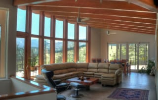 Home rebuilt after wildfire following fire resistant home building standards. Open living room with vaulted ceiling and beams.